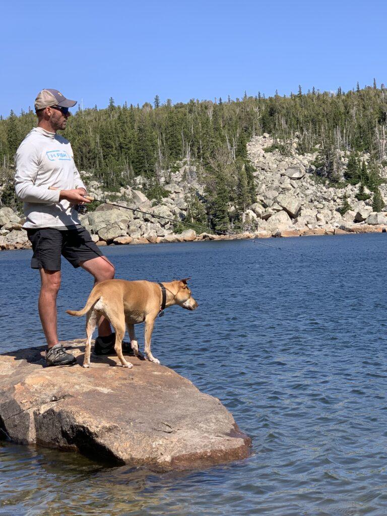 man fishing with dog