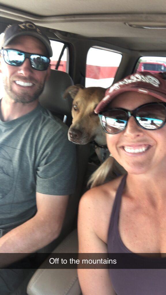 man, dog, woman in vehicle