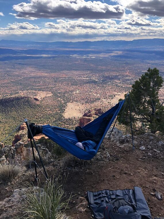 man on cliff with portable hammock stand