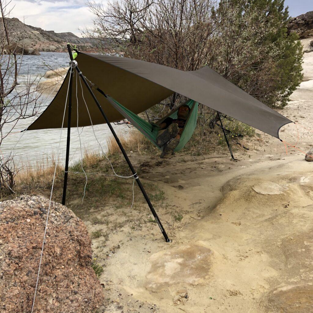 hammock on rocky beach with tarp
